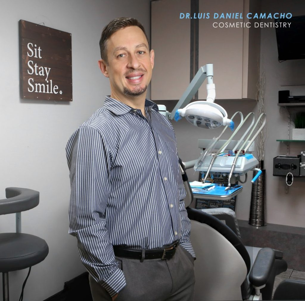 Dr. Luis Camach profile and invisalign picture of waist up with dental chair behind him.
